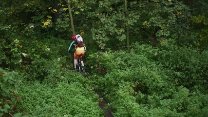 Young girl in helmet riding fast on her mountain bicycle slow