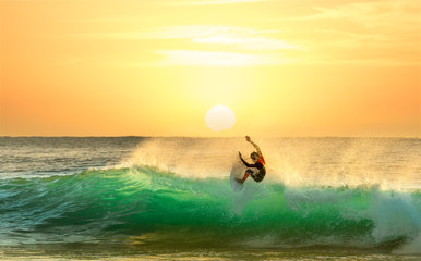 Surfer Surfing at Sunrise