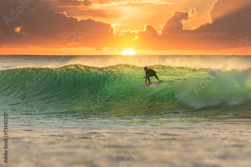Surfer Surfing at Sunrise - 73642307