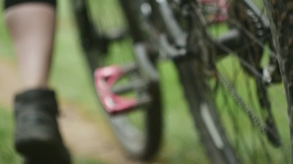 Young girl pushing her mountain bicycle in slow motion