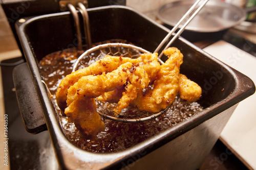 Chicken tenders fried in a deep fryer. - 73643530