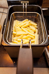 Cooking french fries in a deep fryer basket.
