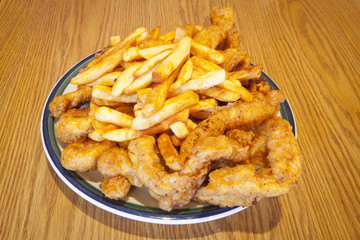 A heaping plate of fried chicken tenders and french fries.