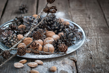 Christmas holiday decoration. Tray with Pine cones and Nuts