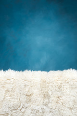 white fur carpet and blue painted wall