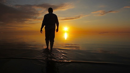 Man looks at the sunset on the Gulf of Finland