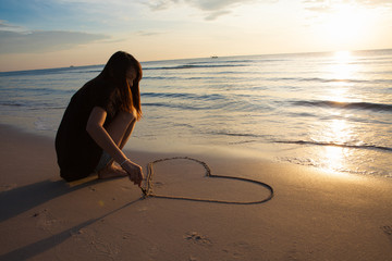 Beautiful woman Drawing heart in the Sand