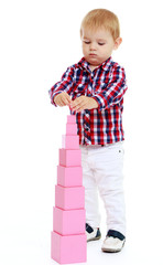 Little boy builds a pyramid in the Montessori school.