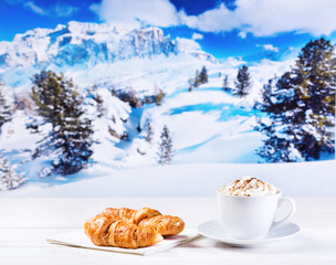 cup of cappuccino with whipped cream and croissants