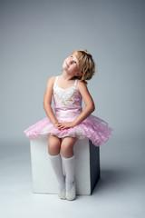 Cute little dancer sitting on cube in studio
