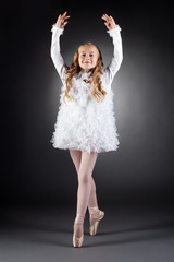 Smiling curly-haired girl dancing on pointes