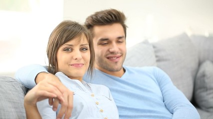 Young couple relaxing in sofa, looking at camera