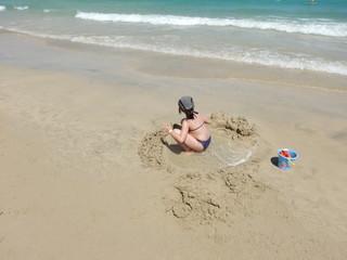 enfant jouant dansle sable d'une plage des canaries