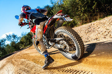 Motocross bike taking off on dirt road.