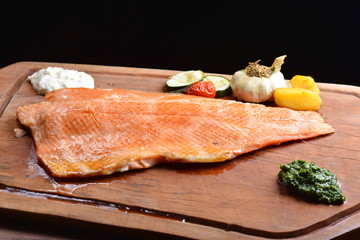 Smoked wild salmon fillet with vegetable on wooden board