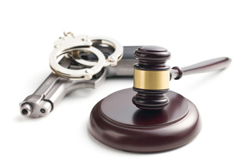 judge's gavel and handgun with handcuffs