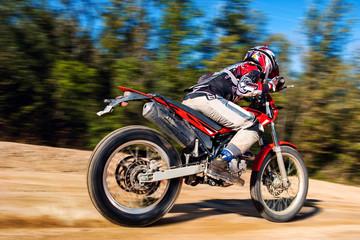 Teen boy riding Motocross bike on gravel road