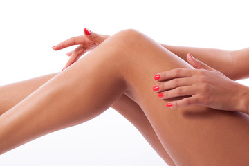 woman's hands with red manicure palming naked legs