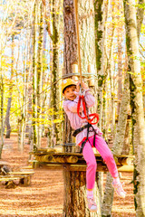 Little girl is zip lining in adventure park