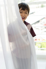 Little boy opening the door curtain