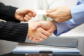 Business clients are exchanging business card  and handshakeing