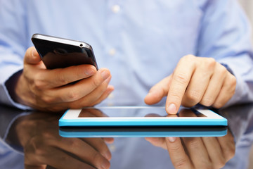 male is using smart mobile phone and tablet computer at the same