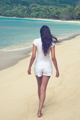 Young Asian woman walking on a tropical beach