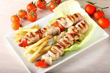 Skewers of mixed meat with french fries and vegetables