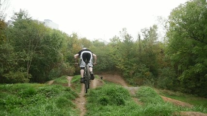 Young girl in helmet jumping on her mountain bicycle slow motion