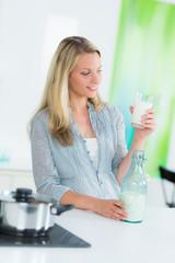 frau steht in der küche und trinkt milch