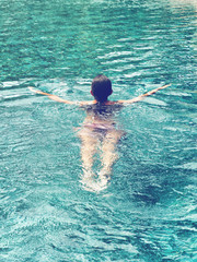Rear view of a woman swimming at the pool
