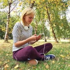Mädchen mit Kopfhörer und Smartphone