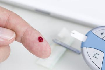 Mann mißt  Blutzucker, im Hintergrund ein Tablet