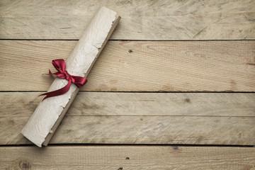 Zusammengerolltes Briefpapier auf Holzhintergrund