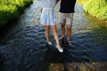 Happy couple running in shallow water. Summertime