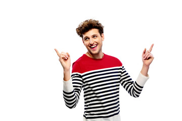 Laughing casual man pointing upwards over white background