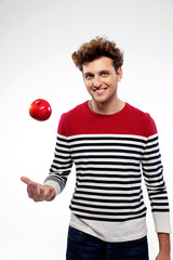 Happy casual young man throwing an apple up