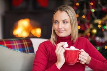 Blonde holding mug and eating marshmallow at christmas