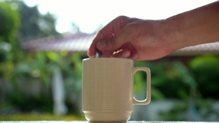 Hand Stiring Steaming Cup of Coffee Outdoors. Slow Motion.