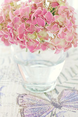 Pink hydrangea flowers in a vase on a colorful table