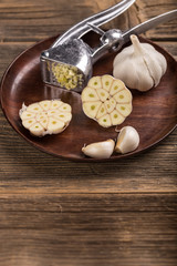 Garlic bulb, clove and press on wooden plate
