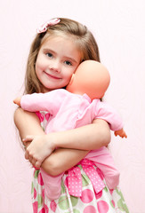 Cute little girl holding and embracing her doll