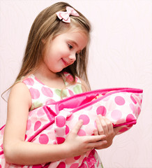 Cute little girl holding her doll