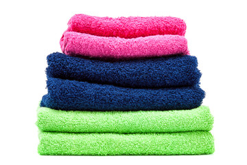Stack of colored towels on white background.