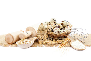 Quail eggs, flour and cooking utensils on canvas on white backgr