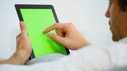 Man websurfing on digital tablet, green screen