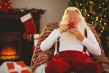 Smiling santa holding  cup of coffee