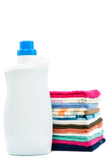 Bottle of detergent and a stack of laundry on white background.