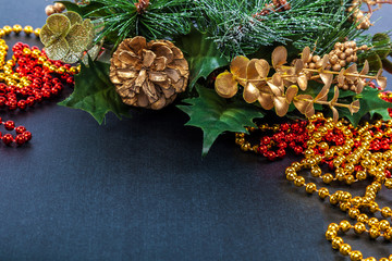 Christmas decoration, fir branch, pine cones, tinsel on a black