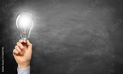 Hand mit Lampe vor einer Tafel - 73660740